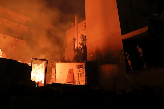 <p>Locals try to extinguish a fire at a nearby house as a wildfire burns at the village of Mati, near Athens, Greece, July 23, 2018. (Photo: Alkis Konstantinidis/Reuters) </p>