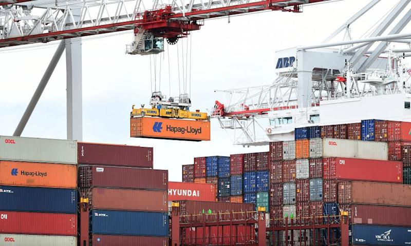 A crane removes containers from a ship.