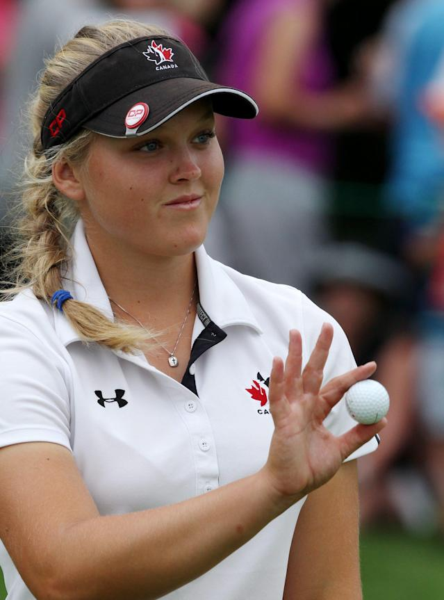 Brooke Henderson, of Canada, responds to the crowd on the 14th hole during final-round play at the Canadian Pacific Women's Open golf tournament in London, Ontario, Sunday, Aug. 24, 2014. (AP Photo/The Canadian Press, Dave Chidley)