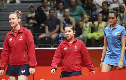 Wales' eleven-year-old table tennis player Anna Hursey, center, walks in with teammate Chloe Thomas, left, and India's Manika Batra before their women's team match the 2018 Commonwealth Games at the Oxenford Studios on the Gold Coast, Australia, Thursday, April 5, 2018. (AP Photo/Rick Rycroft)