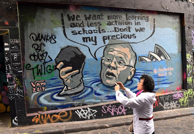 <strong>A mural showing Scott Morrison holding a lump of coal as it advertises a rally by students around the world to protest against climate change.</strong> (Photo: WILLIAM WEST via Getty Images)