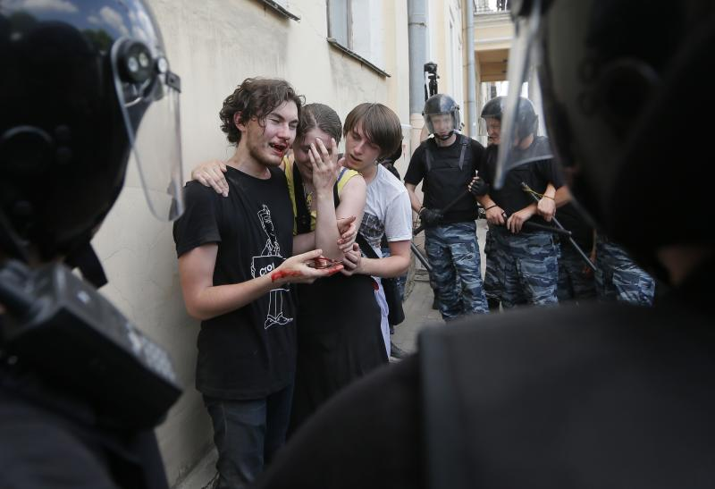 FILE - Riot police guard gay rights activists who were beaten by anti-gay protesters during an authorized gay rights rally in St. Petersburg, Russia, in this Saturday, June 29, 2013 file photo. Elena Mizulina has used her position as the head of the Committee on Family, Women and Children to author increasingly conservative laws, including a new Russian bill outlawing homosexual propaganda that was signed into law in June. A Russian politician with the sober demeanor and tightly-wound bun of an English boarding school headmistress has taken up a new mantel as moral defender of the motherland, vowing to curb gay rights, punish cursing on the web, and halt Russia's demographic decline with, among other things, a divorce tax. (AP Photo/Dmitry Lovetsky, File)