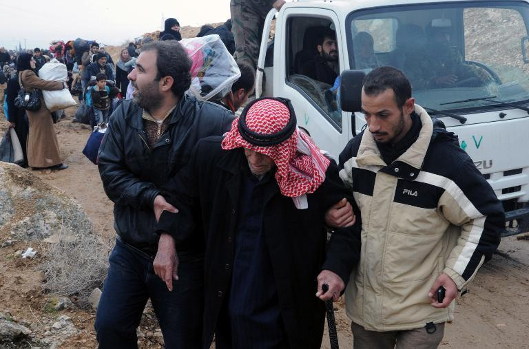Residents of the industrial city of Adra, northeast of Damascus, help an elderly man on December 30, 2013, as they evacuate the area due to fighting between government troops and opposition forces