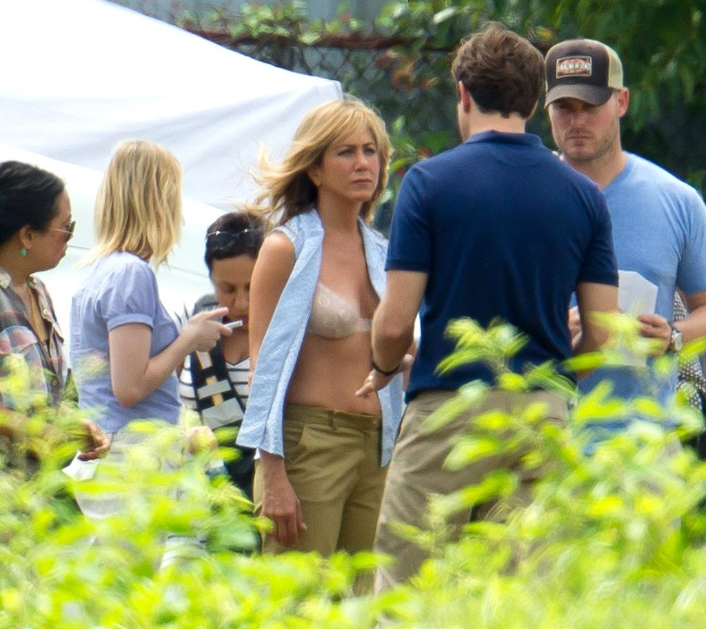 "<b>Bra Bearer</b><br><br>Shirt agape, Jennifer Aniston is seen on the North Carolina set of the comedy ""We're the Millers"" on Monday. A bra-bearing Aniston plays a prostitute in the film, who is convinced by a pot dealer (played by Jason Sudeikis, foreground) to pose as his wife.<br><br>While we don't know exactly why Aniston's shirt is open on the film set, it's probably safe to assume her character has no qualms about it. <br><br>This is not the first time Sudeikis, 36, and Aniston, 43, have led a comedy together: The two also starred in ""Horrible Bosses"" last year."