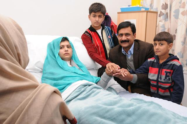 BIRMINGHAM, ENGLAND - OCTOBER 26: (EDITORIAL USE ONLY) In this handout photo provided by the Queen Elizabeth Hospital Birmingham, Malala Yousafzai sits up in her hospital bed with her father Ziauddin and her two younger brothers, Atal Khan (R) and Khushal Khan (C), on October 26, 2012 in Birmingham, United Kingdom. 15 year-old Ziauddin is being treated in the UK after she was shot by the Taliban in Pakistan two weeks ago. (Photo by Queen Elizabeth Hospital Birmingham via Getty Images)
