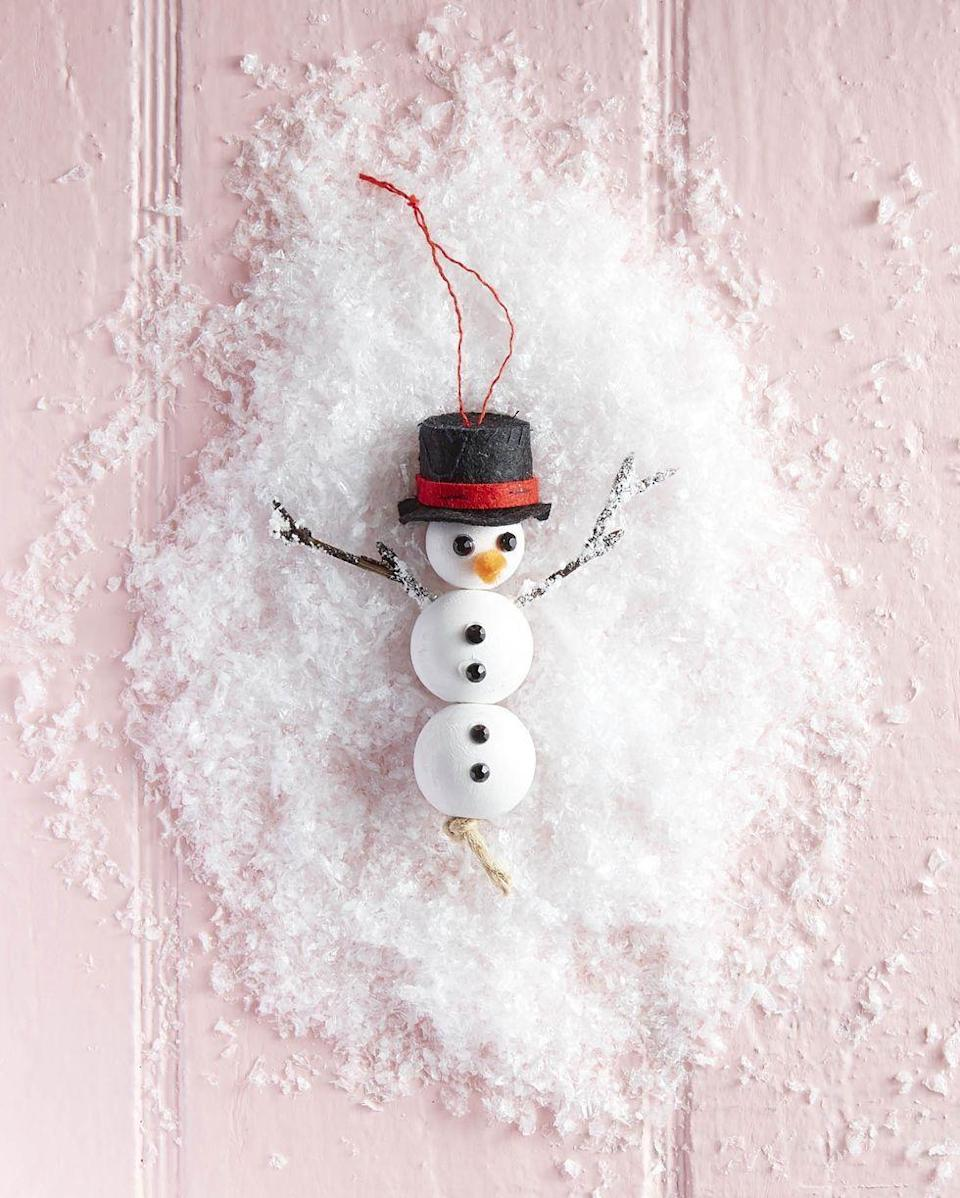 """<p>This jolly happy soul, which can be crafted in no time, shows you care enough to DIY the season's sweetest snowman ornament for them.</p><p><strong>To make:</strong> Paint three wooden craft beads with white acrylic paint. When dry thread a piece twine through the holes of the beads and knot to hold together. Attach two black gem mini crystal rhinestones for the eyes and four for the buttons with hot glue. Snip a short lengths of orange felt and attach just below the eyes with hot glue. Attach stick arms to the side of the middle bead with hot glue. Flock arms, if desired. Wrap a thin length of red felt to a <a href=""""https://www.amazon.com/Sets-Buttons-Snowman-Crafts-DIY/dp/B08H5K1GK7/ref=sr_1_1_sspa?tag=syn-yahoo-20&ascsubtag=%5Bartid%7C10050.g.645%5Bsrc%7Cyahoo-us"""" rel=""""nofollow noopener"""" target=""""_blank"""" data-ylk=""""slk:mini black top hat"""" class=""""link rapid-noclick-resp"""">mini black top hat</a> with hot glue. Glue a string to the top of the hat for hanging. Glue hat to snowman's head.</p><p><a class=""""link rapid-noclick-resp"""" href=""""https://www.amazon.com/TecUnite-Crystal-Rhinestones-Tweezer-Picking/dp/B07FF3GKMN/ref=sr_1_2_sspa?tag=syn-yahoo-20&ascsubtag=%5Bartid%7C10050.g.645%5Bsrc%7Cyahoo-us"""" rel=""""nofollow noopener"""" target=""""_blank"""" data-ylk=""""slk:SHOP BLACK GEM MINI CRYSTAL RHINESTONES"""">SHOP BLACK GEM MINI CRYSTAL RHINESTONES</a></p>"""