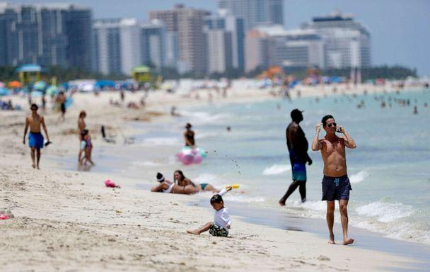 PHOTO: Beach goers walk along the shore on Miami Beach, Florida's famed South Beach, July 7, 2020. Beaches in Miami-Dade County reopened Tuesday after being closed July 3 through 6 to prevent the spread of coronavirus. (Wilfredo Lee/AP)
