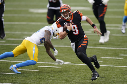 Cincinnati Bengals quarterback Joe Burrow (9) runs past Los Angeles Chargers' Rayshawn Jenkins (23) for a touchdown during the first half of an NFL football game, Sunday, Sept. 13, 2020, in Cincinnati. (AP Photo/Bryan Woolston)