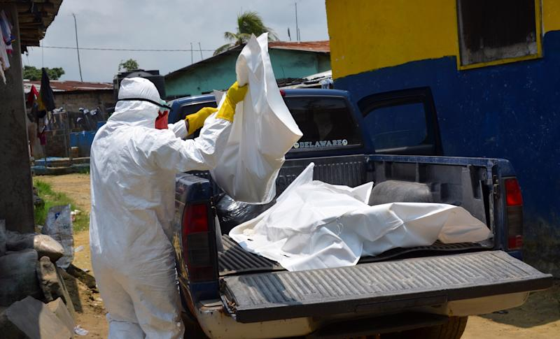 A Liberian Red Cross health worker carries the body of an 18-old-month victim of Ebola on September 12, 2014, in Monrovia, Liberia (AFP Photo/Zoom Dosso)