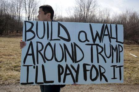 An anti-Trump protester holds his protest sign outside a rally for Republican U.S. presidential candidate Donald Trump in Cleveland, Ohio, March 12, 2016. REUTERS/Rebecca Cook
