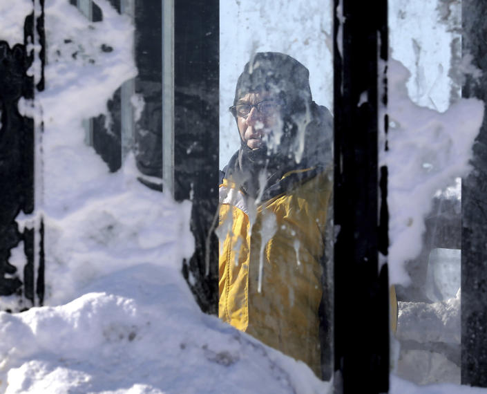 Paul Kollauf is framed by an accumulation of snow on the panes of a bus shelter while waiting for a bus on East Washington Avenue in Madison, Wis., on Jan. 30, 2019. (Photo: John Hart/Wisconsin State Journal via AP)