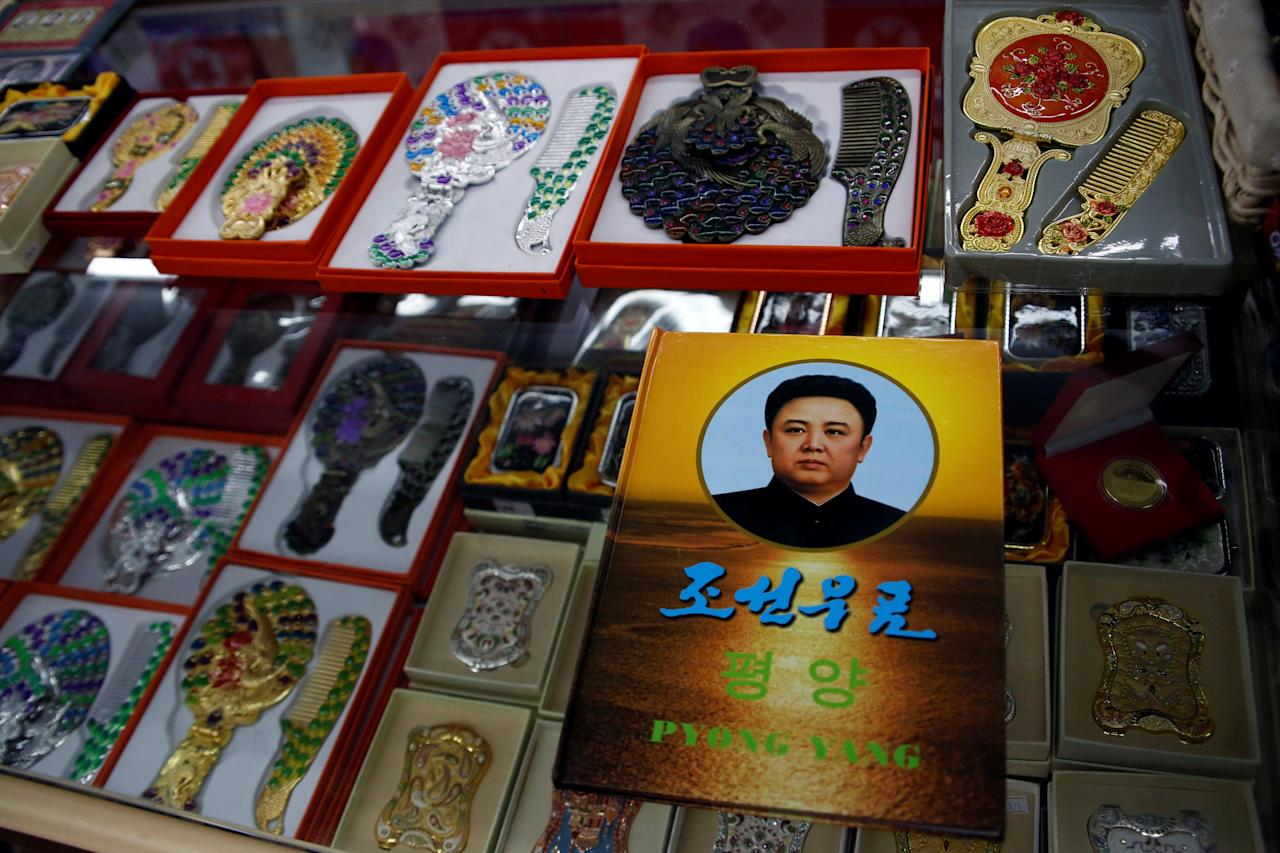 "A stamp album with a portrait of the late North Korean leader Kim Jong-il is on display in a souvenir shop in Dandong, Liaoning province, China, across the border from North Korea, September 12, 2016.  The Korean writing reads, ""Korean stamps"". REUTERS/Thomas Peter"
