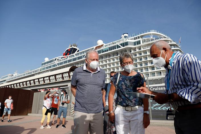 This image shows two people looking at a piece of paper another person is holding in front of a cruise ship.