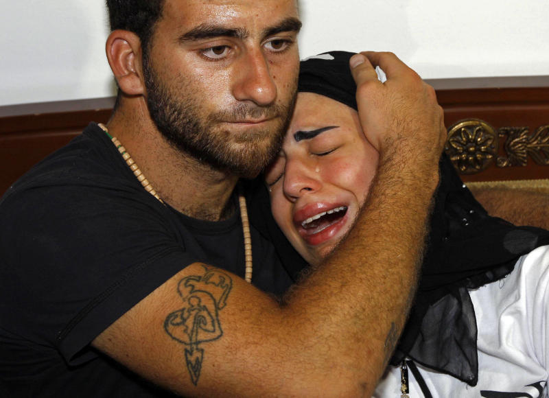 Fatima, right, daughter of Mohammed Darrar Jammo a Syrian political analyst and one of Syrian President Bashar Assad's strongest defenders, who was gunned down inside his home, is comforted by a relative as she mourns her father, in the southern coastal town of Sarafand, Lebanon, Wednesday, July 17, 2013. Clashes between pro and anti-Syrian groups in Lebanon have left scores of people dead in the past months in a spillover of Syria's civil war into its smaller neighbor. (AP Photo/Mohammed Zaatari)