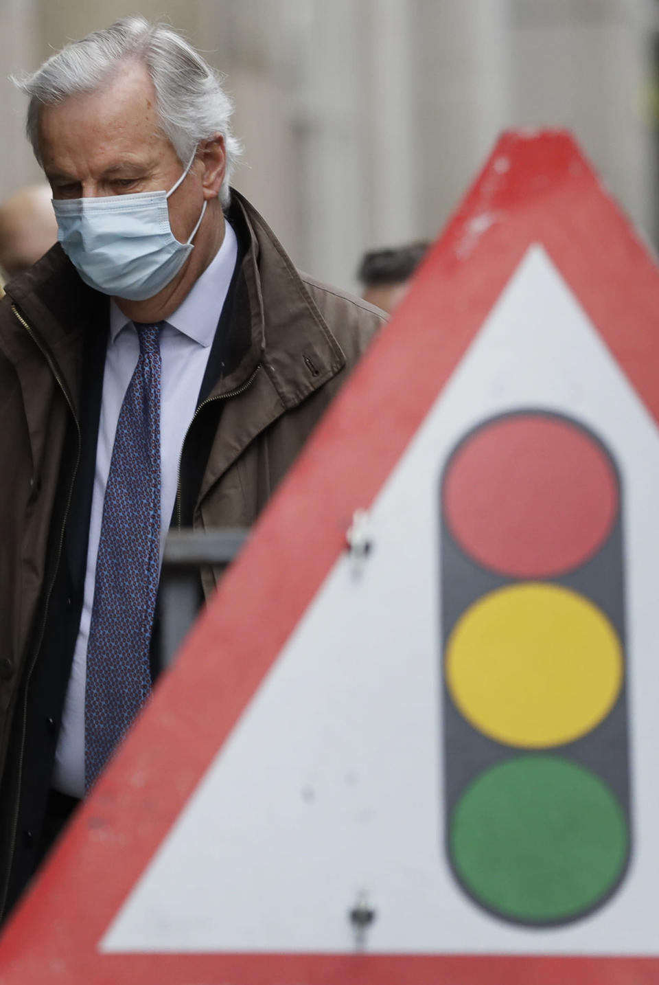 EU Chief Negotiator Michel Barnier passes a traffic sign as he walks to a conference centre in Westminster in London, Sunday, Nov. 29, 2020. Teams from Britain and the European Union are continuing face-to-face talks on a post-Brexit trade deal in the little remaining time. (AP Photo/Kirsty Wigglesworth)