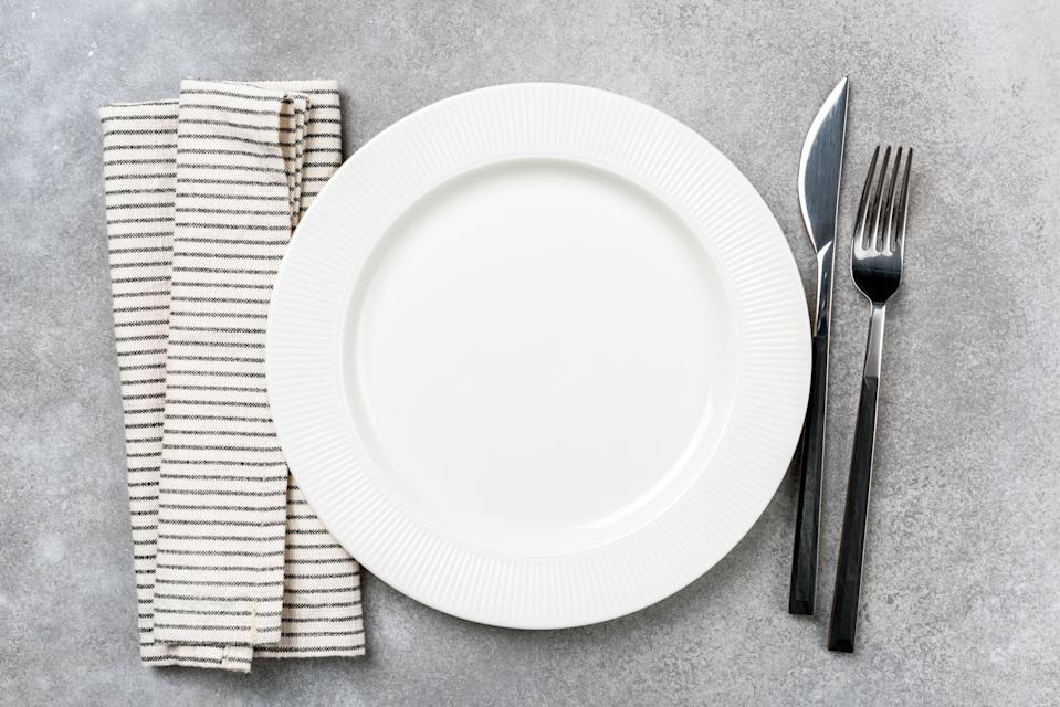 Table setting for dinner: empty plate, linen cloth and silverware. Top view, copy space