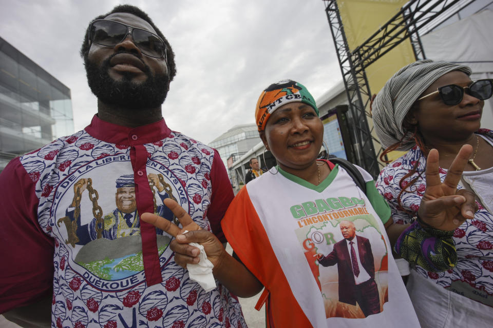 Supporters of former Ivory Coast President Laurent Gbagbo gather at the Brussels international airport in Brussels, Thursday, June 17, 2021. The former Ivory Coast president Laurent Gbagbo is returning home to Ivory Coast for the first time in nearly a decade, after his acquittal on war crimes charges was upheld at the International Criminal Court earlier this year. (AP Photo/Olivier Matthys)