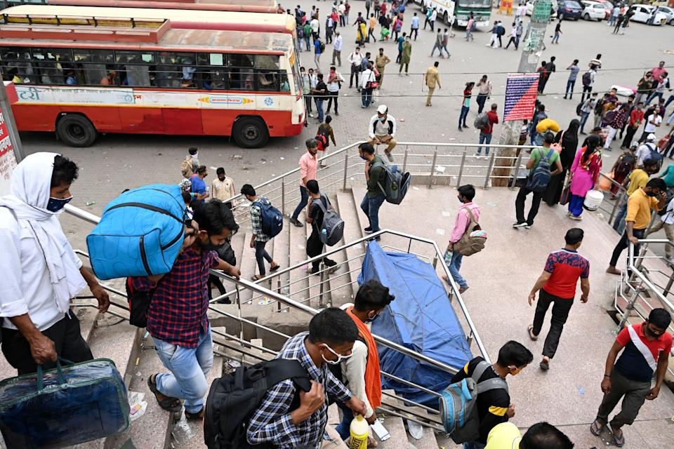 People arrive at a bus station in New Delhi on April 20, 2021, to leave for their native places as India battles a record-breaking spike in Covid-19 coronavirus infections that has forced the capital into a week-long lockdown. (Photo by Sajjad HUSSAIN / AFP) (Photo by SAJJAD HUSSAIN/AFP via Getty Images)
