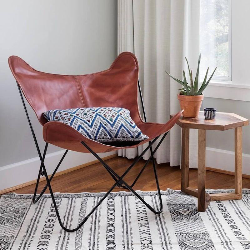 "This butterfly chair is an icon of modern design, but still brings an incomparable level of comfort with its soft leather. Get it at <a href=""https://www.the-citizenry.com/products/palermo-butterfly-chair-iron"" target=""_blank"">The Citizenry</a>."