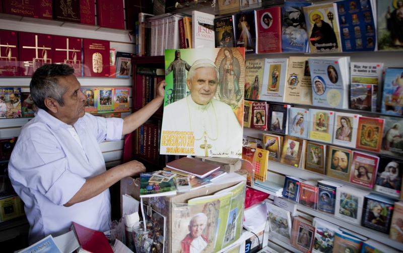 Seller Jorge Sanchez shows an image of Pope Benedict XVI at a religious store near to the Basilica of Guadalupe in Mexico City, Monday, Feb. 11, 2013. Pope Benedict XVI announced Monday that he would resign Feb. 28, the first pontiff to do so in nearly 600 years. The decision sets the stage for a conclave to elect a new pope before the end of March. (AP Photo/Eduardo Verdugo)