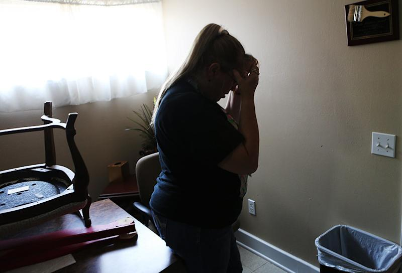 Mary <strong></strong>Woods holds her head in her hands as she shows off some of the damage Harvey left at the domestic violence shelter she works at in Humble, Texas. (Andy Campbell/HuffPost)