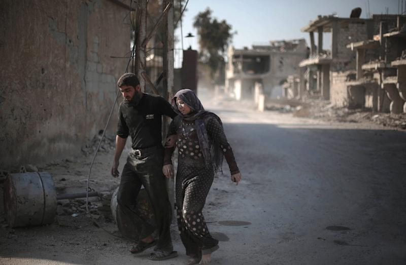 A Syrian man escorts his injured wife following reported air strikes by regime forces on the town of al-Nashabiyah in the eastern Ghouta region, on December 14, 2015