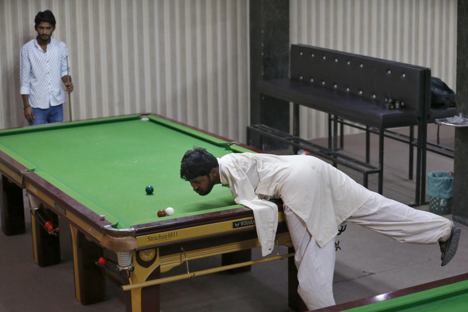 Mohammad Ikram plays snooker with his chin at a local snooker club in Samundri town, Pakistan, Sunday, Oct. 25, 2020. Ikram, 32, was born without arms, but everyone simply admires his snooker skills when he hits the cue ball with his chin and pots a colored ball on a snooker table. He lives in a remote rural town of Punjab province and his physical disability doesn't come in his way to fulfil his childhood dream of playing the game of snooker. (AP Photo/Anjum Naveed)