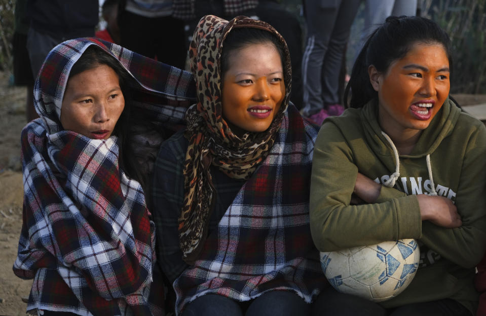 Tangkhul Naga girls watch a friendly football match between villages in Shangshak, in the northeastern Indian state of Manipur, Saturday, Jan. 30 2021. In most of India, cricket is the only sport that matters. But for the Nagas, it is soccer. The region is ethnically distinct from everywhere else, and plagued by a decades-long fight for independence. (AP Photo/Yirmiyan Arthur)