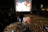 People lay candles near a picture of swimming gold medallist Camille Muffat on March 10, 2015 in her hometown of Nice, France
