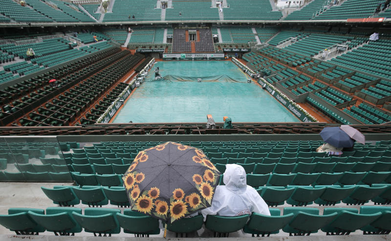 Spectator sit under an umbrella on center court as matches were delayed because of the rain for the French Open tennis tournament at the Roland Garros stadium Tuesday, May 28, 2013 in Paris. (AP Photo/Christophe Ena)