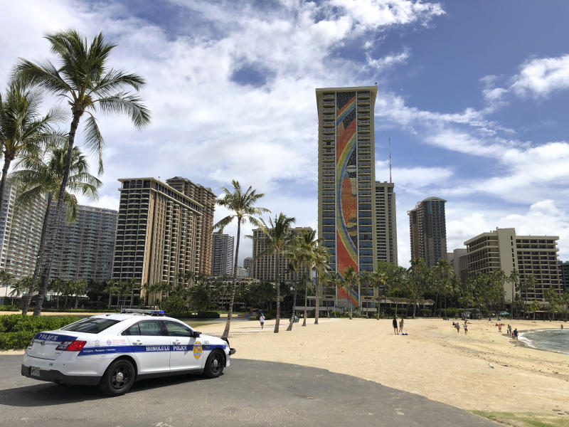 A police officer arrives to tell people to leave Waikiki Beach in Honolulu on Saturday, March 28, 2020. Like many cities across the world, Honolulu came to an eerie standstill this weekend as the coronavirus pandemic spread throughout the islands. But Hawaii officials went beyond the standard stay-at-home orders and effectively flipped the switch on the state's tourism-fueled economic engine in a bid to slow the spread of the virus. As of Thursday, anyone arriving in Hawaii must undergo a mandatory 14-day self-quarantine. The unprecedented move dramatically reduced the number of people on beaches, in city parks and on country roads where many people rely on tourism to pay for the high cost of living in Hawaii. (AP Photo/Caleb Jones)