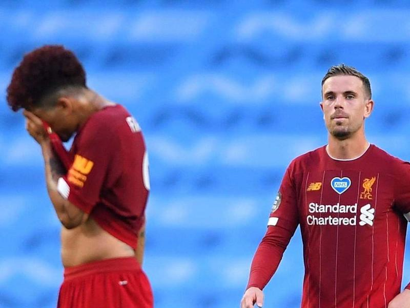 Jordan Henderson, right, reacts after Manchester City's third goal: Getty