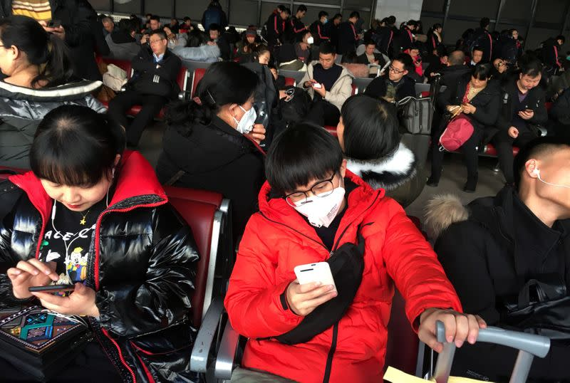 Passengers wearing masks are seen at the waiting area for a train to Wuhan at the Beijing West Railway Station, in Beijing