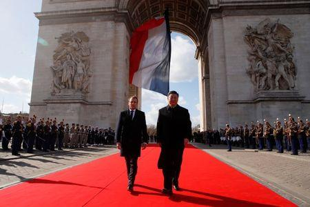 French President Emmanuel Macron and his Chinese counterpart Xi Jinping leave the Arc de Triomphe monument after attending a wreath laying ceremony at the Tomb of the Unknown soldier, in Paris