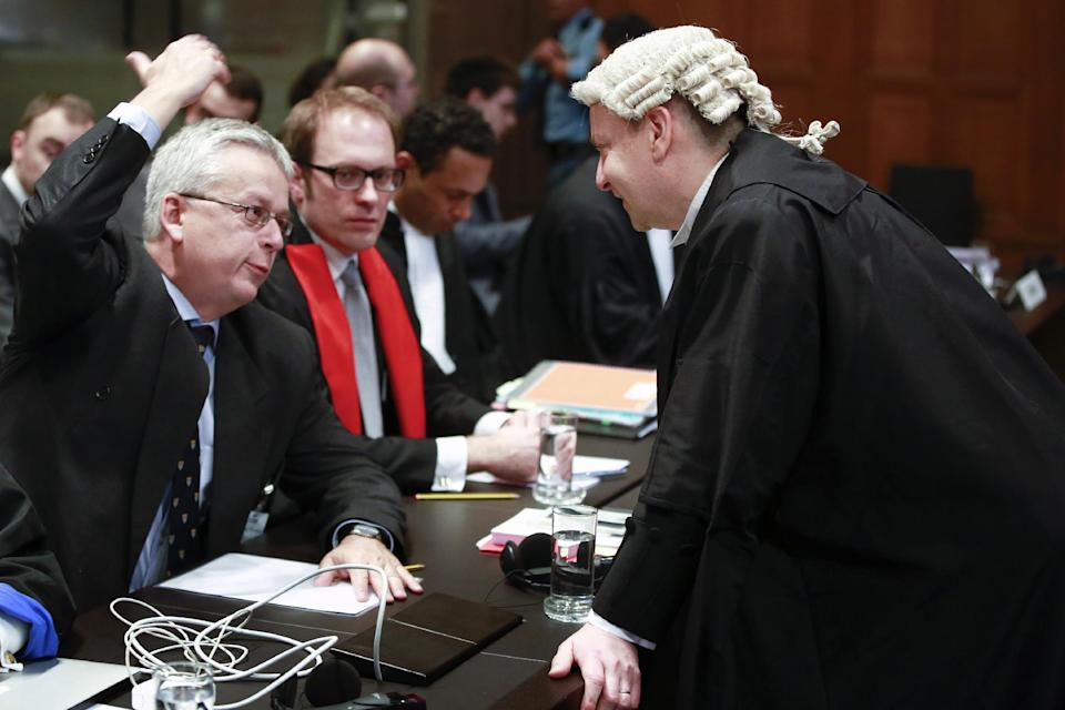 Counsel Philippe Sands of Croatia, right, speaks with Andreas Zimmermann of the Serbian delegation, left, prior to the start of public hearings at the International Court of Justice (ICJ) in The Hague, Netherlands, Monday, March 3, 2014. Croatia is accusing Serbia of genocide during fighting in the early 1990's as the former Yugoslavia shattered in spasms of ethnic violence, in a case at the United Nations' highest court that highlights lingering animosity in the region. Croatia is asking the ICJ to declare that Serbia breached the 1948 Genocide Convention when forces from the former Federal Republic of Yugoslavia attempted to drive Croats out of large swaths of the country after Zagreb declared independence in 1991. (AP Photo/Jiri Buller)