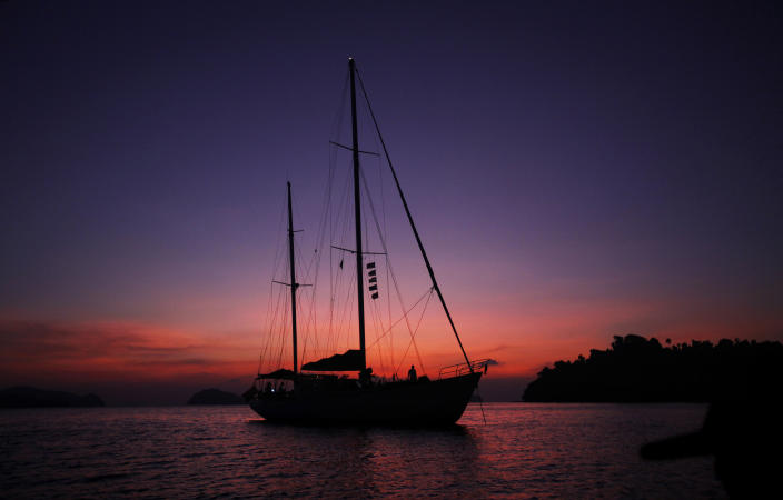 In this Feb. 9, 2014 photo, Meta IV, a $1 million yacht offering cruises among the reefs and islands, is silhouetted at sunset near Nyuang Wee Island, in Mergui Archipelago, Myanmar. Isolated for decades by the country's former military regime and piracy, the Mergui archipelago is thought by scientists to harbor some of the world's most important marine biodiversity and looms as a lodestone for those eager to experience one of Asia's last tourism frontiers before, as many fear, it succumbs to the ravages that have befallen many of the continent's once pristine seascapes. (AP Photo/Altaf Qadri)