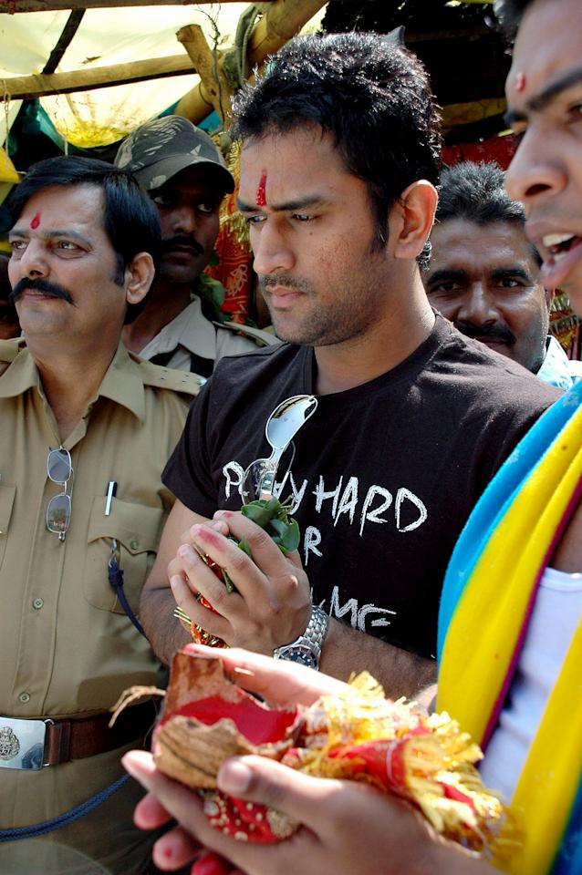 Captain of the Indian cricket team, Mahendra Singh Dhoni, (C) performs a religious rite beside his new car in Ranchi, 26 october 2007.  The car, a Toyota, was given to Dhoni as a gift by the government of the Indian state of Jharkhand. AFP PHOTO/STR