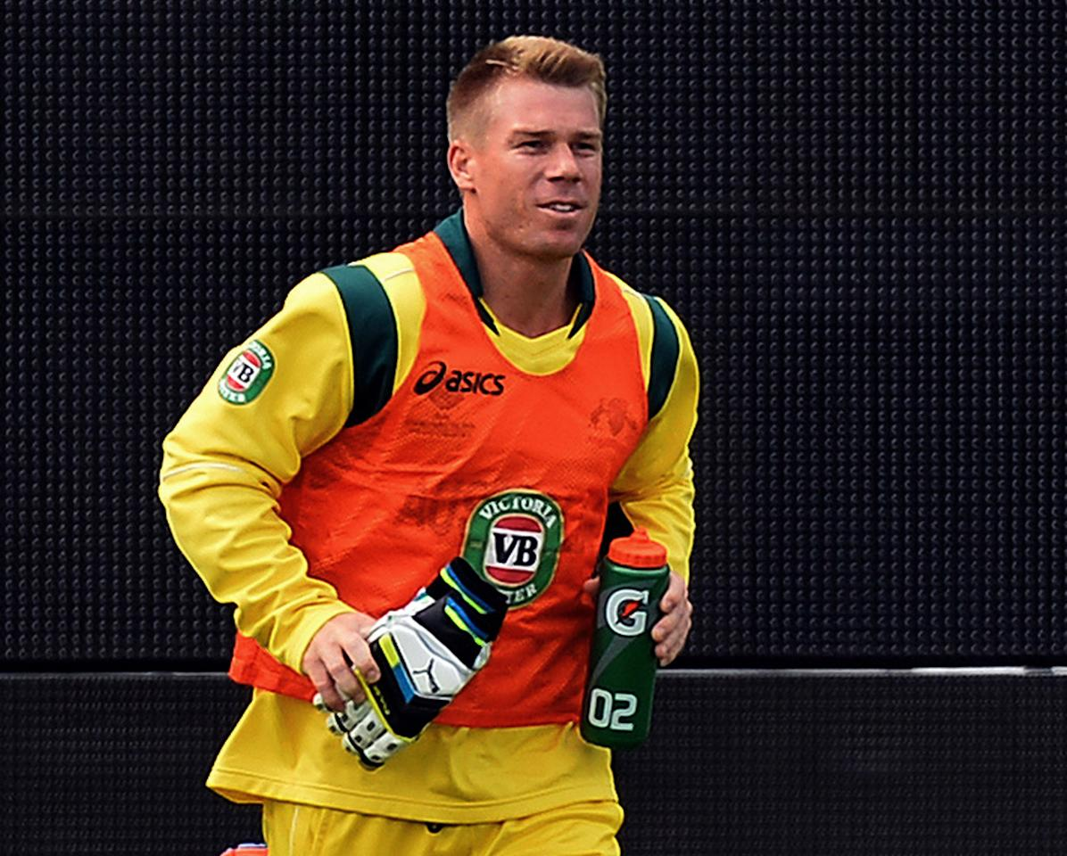 Australia's David Warner carries water onto the pitch for his teammates during the 2013 ICC Champions Trophy One Day International (ODI) cricket match between Australia and New Zealand at Edgbaston in Birmingham, central England on June 12, 2013.  Australia won the toss and elected to bat first.  Australia batsman David Warner has been dropped for the country's Champions Trophy match against New Zealand on Wednesday, after allegedly being involved in a late-night tussle with an England player, Cricket Australia said.  AFP PHOTO/Paul ELLIS - RESTRICTED TO EDITORIAL USE        (Photo credit should read PAUL ELLIS/AFP/Getty Images)