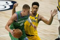 Dallas Mavericks center Kristaps Porzingis (6) works against Indiana Pacers guard Malcolm Brogdon (7) for a shot during the first half of an NBA basketball game in Dallas, Friday, March 26, 2021. (AP Photo/Tony Gutierrez)