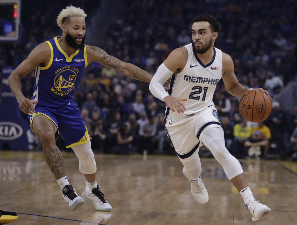 Memphis Grizzlies' Tyus Jones, right, drives the ball against Golden State Warriors' Ky Bowman (12) in the first half of an NBA basketball game Monday, Dec. 9, 2019, in San Francisco. (AP Photo/Ben Margot)
