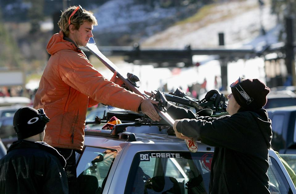 Jordan Zdknek of Silverthorne, Colorado unloads the skis and snowboards from the roof rack as he and his friends prepare for opening day at Arapahoe Basin Ski Area.