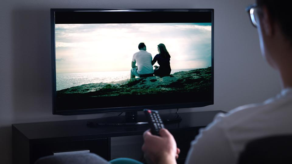 Man watching tv or streaming movie or series with smart tv at home.