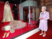 <p>In celebration of her milestone marriage to her husband, a summer exhibition was held at Buckingham Palace that featured the couple's wedding outfits. She wore a gown and a 13-foot bridal trail designed by Norman Hartnel while Prince Philip donned a naval uniform.<br></p>