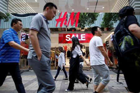 FILE PHOTO: People walk past a H&M fashion chain store at Tsim Sha Tsui shopping district in Hong Kong