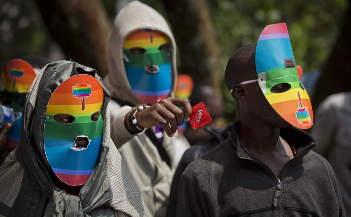 """FILE - In this Monday, Feb. 10, 2014 file photo, Kenyan gays and lesbians and others supporting their cause wear masks to preserve their anonymity and one holds out a condom, as they stage a rare protest, against Uganda's increasingly tough stance against homosexuality and in solidarity with their counterparts there, outside the Uganda High Commission in Nairobi, Kenya. Ugandan President Yoweri Museveni met in his office with a team of U.S.-based rights activists concerned about legislation that would impose life sentences for some homosexual acts and made clear he had no plans to sign the bill, according to Santiago Canton of the Robert F. Kennedy Center for Justice and Human Rights who attended the Jan. 18, 2014 meeting, but one month later Museveni appears to have changed his mind, saying through a spokesman in February 2014 that he would sign the bill """"to protect Ugandans from social deviants."""" (AP Photo/Ben Curtis, File)"""