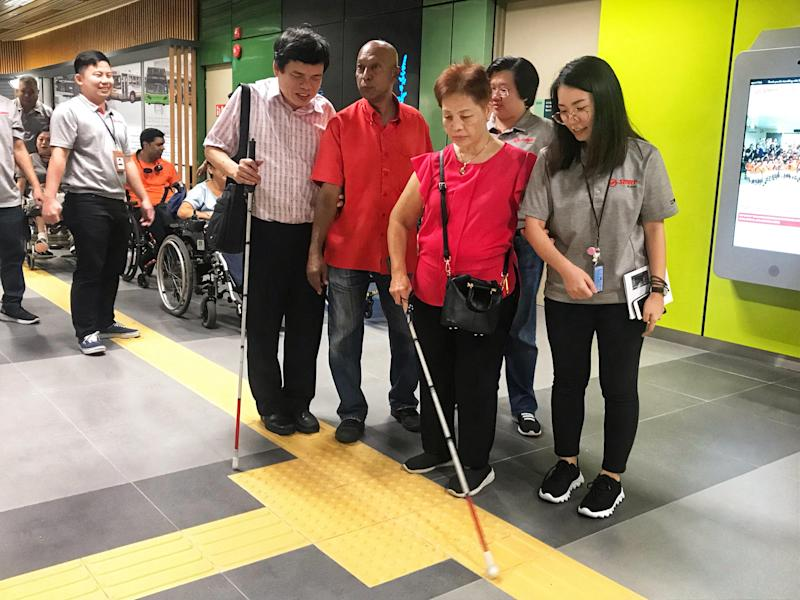 SMRT staff members assisting visually-impaired commuters at the hub on 23 August, 2019. (PHOTO: SMRT)
