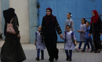 Women walk with their children on the first day of the new school year at the United-Nation run Elementary School at the Shati refugee camp in Gaza City, Saturday, Aug. 8, 2020. Schools run by both Palestinian government and the U.N. Refugee and Works Agency (UNRWA) have opened almost normally in the Gaza Strip after five months in which no cases of community transmission of the coronavirus had been recorded. (AP Photo/Adel Hana)