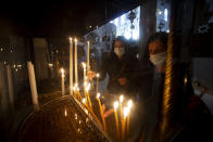 Christian worshippers light candles in the Church of the Nativity, traditionally believed to be the birthplace of Jesus Christ, in the West Bank city of Bethlehem, Monday, Nov. 23, 2020. Normally packed with tourists from around the world at this time of year, Bethlehem resembles a ghost town – with hotels, restaurants and souvenir shops shuttered by the pandemic. (AP Photo/Majdi Mohammed)