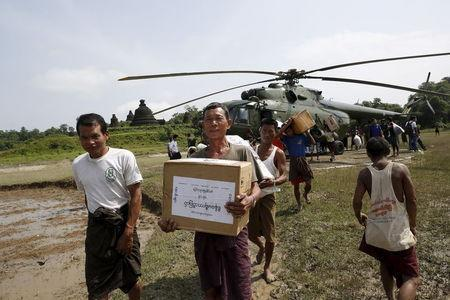 Storm victims carry aid from a military helicopter at Mrauk-U township, Rakhine state, August 5, 2015. REUTERS/Soe Zeya Tun