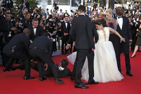 """A man is arrested by security as he tries to slip under the dress of actress America Ferrera (3rdR) as she poses on the red carpet arriving for the screening of the film """"How to Train Your Dragon 2"""" out of competition at the 67th Cannes Film Festival in Cannes May 16, 2014. REUTERS/Benoit Tessier"""